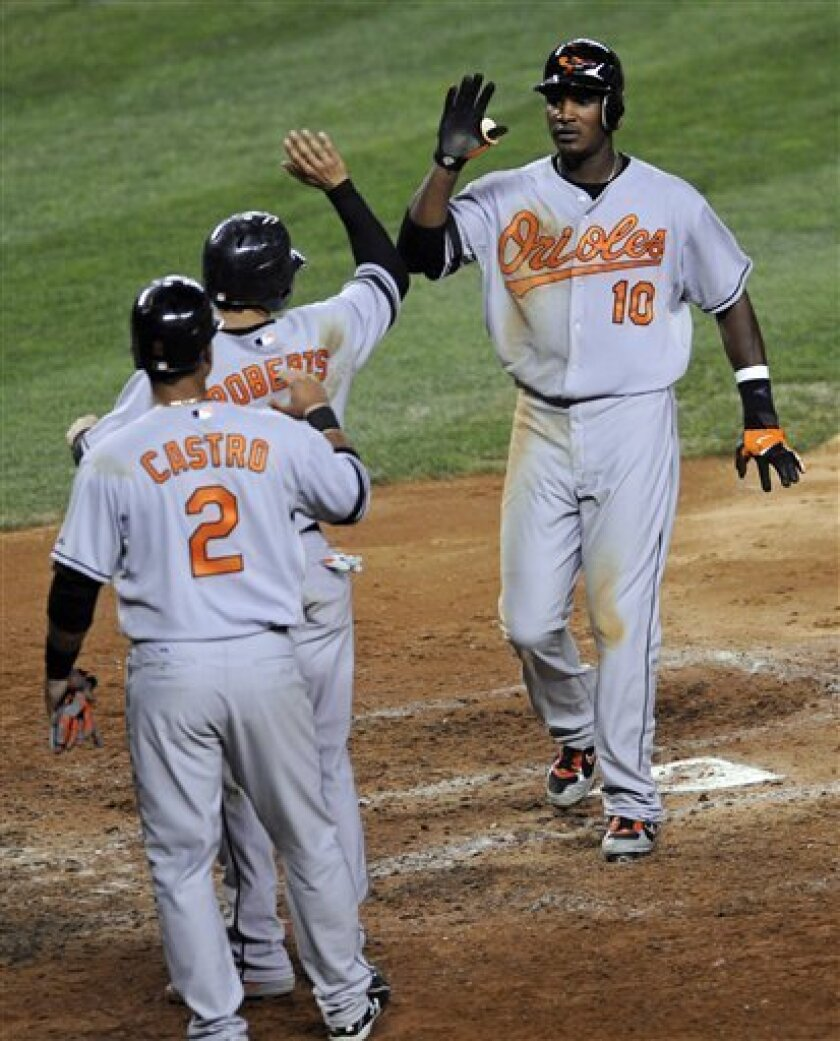 Baltimore Orioles' Adam Jones (10) is greeted by Juan Castro (2) and Brian Roberts as he comes home after hitting a grand slam against the New York Yankees during the sixth inning of a baseball game Monday, July 28, 2008 at Yankee Stadium in New York. (AP Photo/Bill Kostroun)