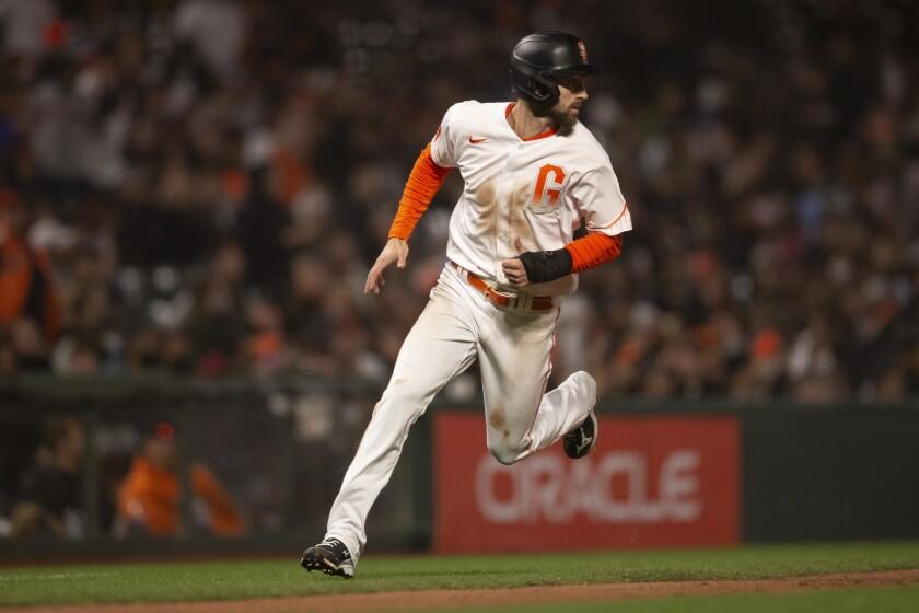 El jugador de los Gigantes de San Francisco, Steven Duggar, pasa por tercera base mientras corre al plato en un sencillo remolcador de Tommy LaStella en el cuarto inning del juego de la MLB que enfrentó a su equipo con los Padres de San Diego, el 14 de septiembre de 2021, en San Francisco. (AP Foto/D. Ross Cameron)