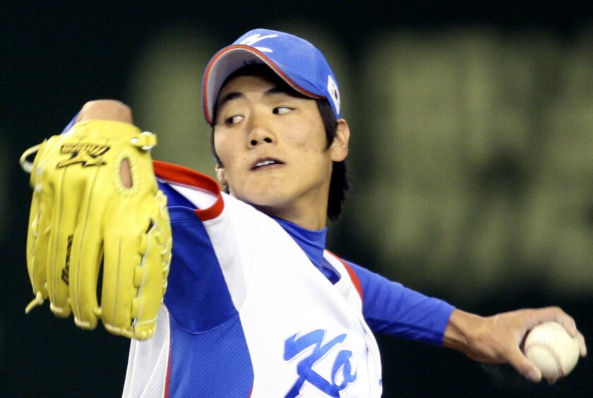 Team South Korea pitcher Kim Kwang-hyun winds up to pitch against the Saitama Seibu Lions in the fifth inning of their exhibition game for the World Baseball Classic at Tokyo Dome in Tokyo, Japan, Monday, March 2, 2009. (AP Photo/Koji Sasahara)