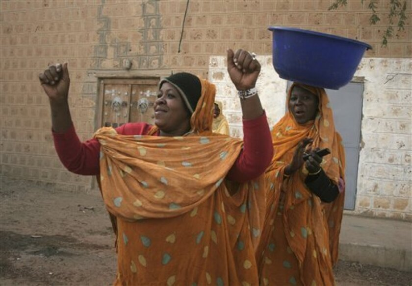 Women dance openly in front of a photographer as they walk along a street in Timbuktu, Mali, Thursday Jan. 31, 2013. Many things have changed in Timbuktu since the Islamic militants ceased to enforce their law and relinquished power to French special forces who parachuted in several days ago, liberating this storied city, and now there is a growing sense of freedom. (AP Photo/Harouna Traore)