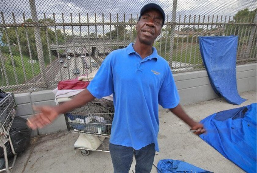 Tommy Forrest, 54, prepared to set up his tent on the Island Avenue bridge over Interstate 5 in downtown San Diego. Forrest said he lost a kitchen job last year. (John R. McCutchen / Union-Tribune)