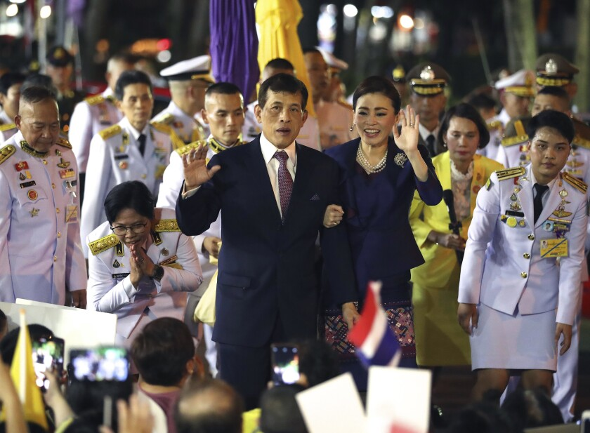 Thai King Maha Vajiralongkorn and Queen Suthida wave to supporters at the opening of a mass transit station