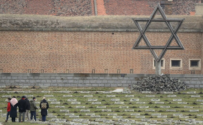 In this Thursday Jan. 24, 2019 file photo visitors walk through the cemetery of the former Nazi concentration camp in Terezin, Czech Republic. The antisemitic incidents in the Czech Republic continued to rise last year, the Jewish community said Wednesday June 9, 2021. In its annual report, the Federation of the Jewish Communities said it registered 874 antisemitic attacks in 2020, 180 more than the previous year. (AP Photo/Petr David Josek, file)