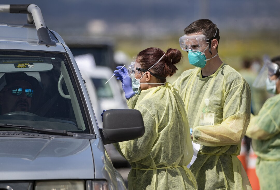 Riverside County medical personnel administer a coronavirus test to a driver at a drive-though testing facility at Diamond Stadium.