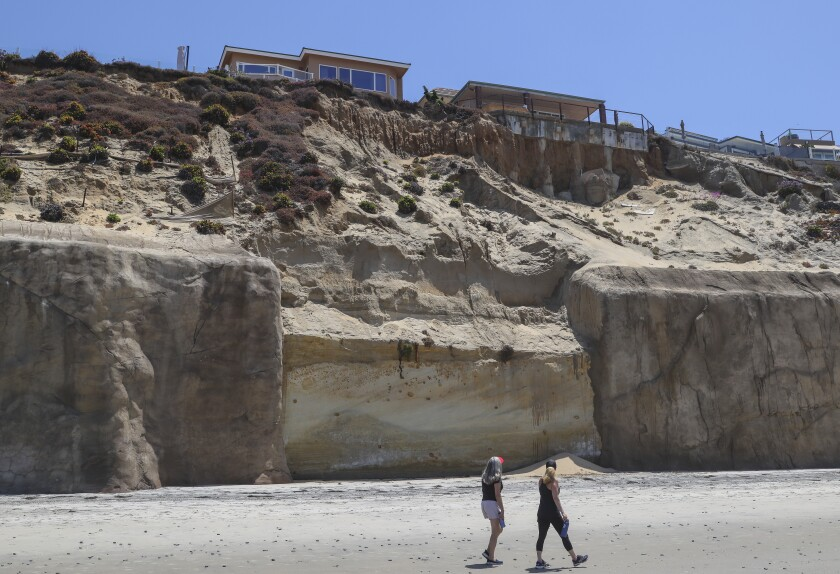 Two people walk past a section of bluff without a sea wall near 245 Pacific Ave. in Solana Beach at low tide Friday.