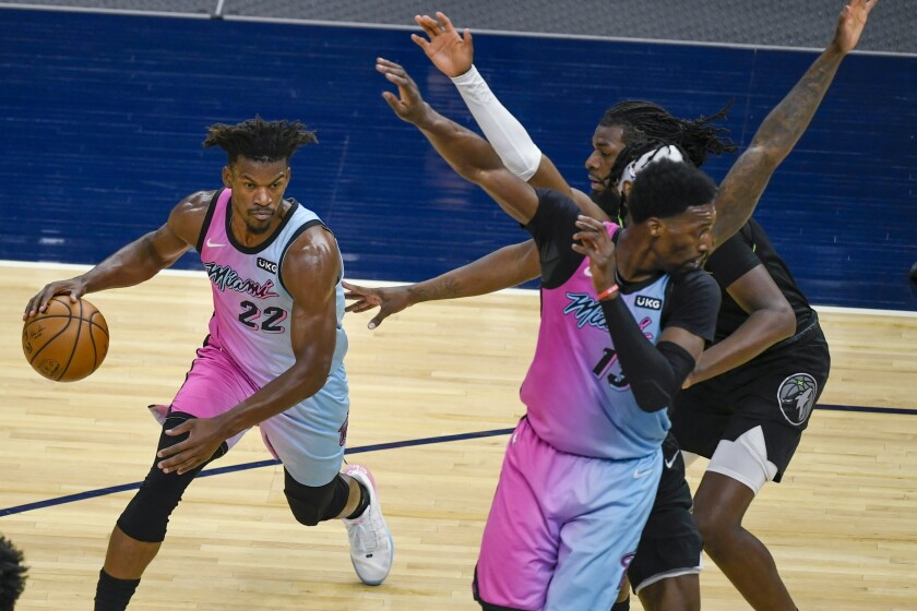 Miami Heat forward Jimmy Butler (22) drives past a crowd of Minnesota Timberwolves defenders as Heat center Bam Adebayo, right front, tries to set a pick during the first half of an NBA basketball game Friday, April 16, 2021, in Minneapolis. (AP Photo/Craig Lassig)