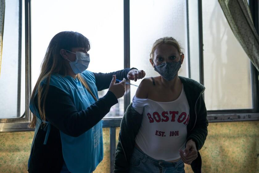 Una enfermera vacuna a María Rosa con una dosis de la vacuna Sinopharm para el COVID-19 en el barrio Fuerte Apache en la provincia de Buenos Aires, Argentina, el miércoles 18 de agosto de 2021. (AP Foto/Víctor R. Caivano)