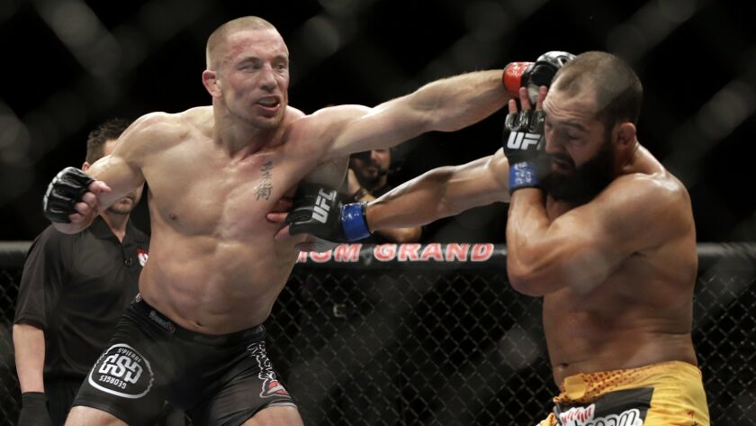 Johny Hendricks, right, exchanges punches with Georges St-Pierre during a UFC 167 in Las Vegas on Nov. 16, 2013. St-Pierre won by split decision.