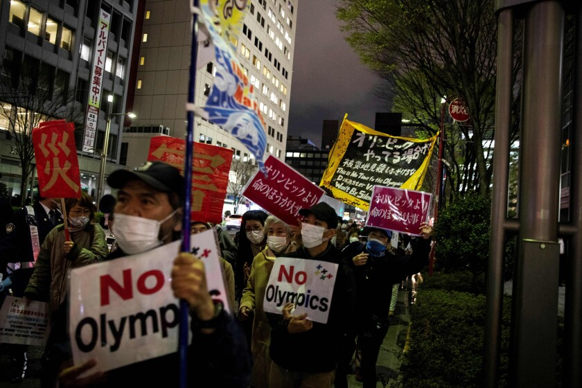 People demonstrate as they hold slogans against the Tokyo 2020 Olympic Games