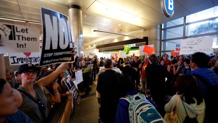 People protest President Trump's travel ban at Los Angeles International Airport on Sunday.