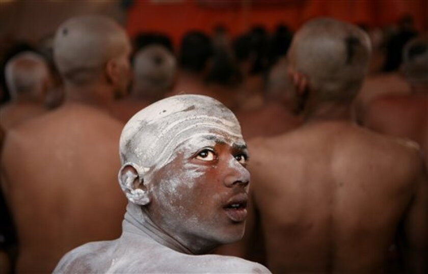 In this Feb. 6, 2013 file photo, a Naga Sadhu, center, watches as other Hindu holy men of the Juna Akhara sect participate in a ritual that is believed to rid them of all ties in this life and dedicate themselves to serving God as a Naga or naked holy men, at Sangam, the confluence of the Ganges an
