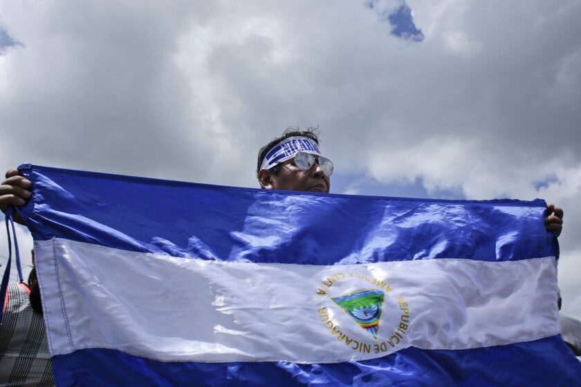FILE - In this July 30, 2018 file photo, a protester holds up a Nicaraguan flag during a demonstration supporting journalists recently attacked while covering protests demanding the resignation of President Daniel Ortega and the release of all political prisoners, in Managua, Nicaragua. The Trump administration is sanctioning three Nicaraguan officials accused of human rights abuses, election fraud and corruption, announced on Thursday, Nov. 7, 2019 by the U.S. Department of Treasury's Office of Foreign Assets Control. (AP Photo/Arnulfo Franco, File)