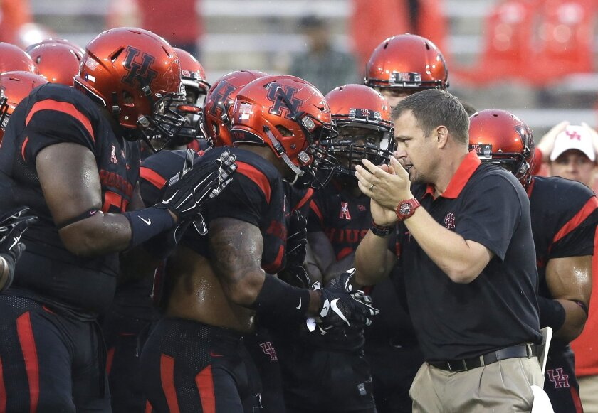 FILE - In this Oct. 31, 2015, file photo, Houston coach Tom Herman, right, encourages his players before an NCAA college football game against Vanderbilt in in Houston. After Connecticut ended Houston's unbeaten season last week, the Cougars head into Friday's regular-season finale with the unenviable job of trying to slow down No. 16 Navy. Herman said the 20-17 loss to the Huskies was tough, but Houston has to get over it quickly. (AP Photo/Pat Sullivan, File)