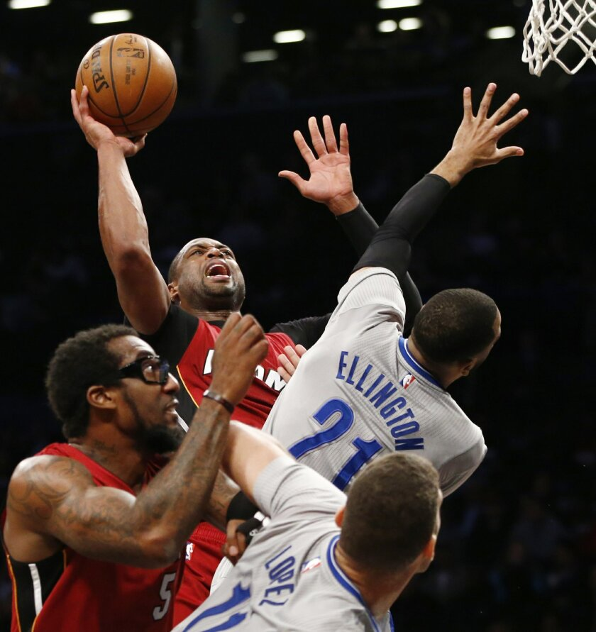 Miami Heat guard Dwyane Wade (3) shoots as Brooklyn Nets guard Wayne Ellington (21) defends, while Miami Heat center Amare Stoudemire and Nets center Brook Lopez (11) wait for a rebound during the first half of an NBA basketball game Tuesday, Jan. 26, 2016, in New York. (AP Photo/Kathy Willens)