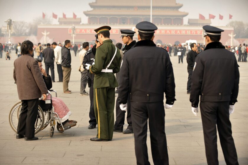 In this 2008 file photo, Chinese police stop and search a man in Tiananmen Square. Police brutality -- and impunity -- is a major issue in China, where the Communist party exercises absolute control over not only the police, but also the courts and media.