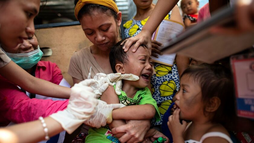 A Philippine Red Cross worker administers a measles vaccine in Manila.