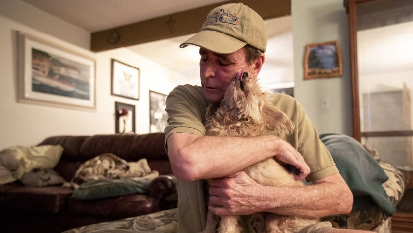 Paul Hoffman holds Buddy, a 14-year-old blind dog on Thursday, November 29. Hoffman has taken in Bud