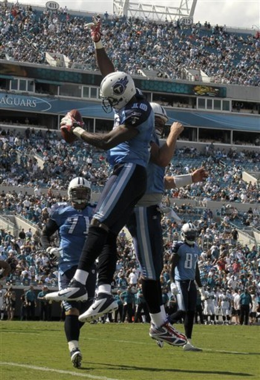 Tennessee Titans wide receiver Kenny Britt (18), second from left, celebrates with quarterback Matt Hasselbeck, second from right, after catching a two-yard touchdown pass in the end zone during the second half of an NFL football game against the Jacksonville Jaguars in Jacksonville, Fla., Sunday, Sept. 11, 2011. Titans tackle Michael Roos (71), left, and Tennessee Titans wide receiver Lavelle Hawkins (87) look on. The Jaguars won 16-14.(AP Photo/PHELAN EBENHACK)