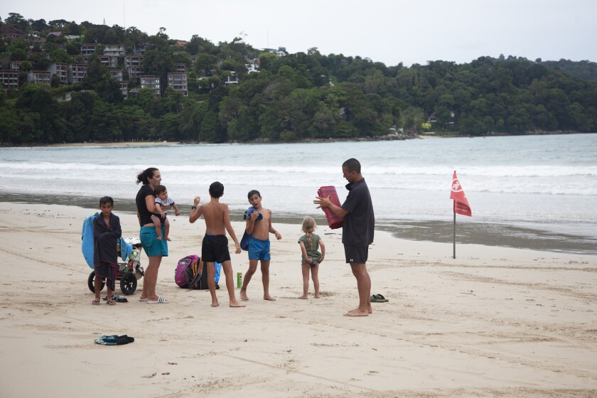 In this Wednesday, July 7, 2021, photo, tourist Liron Or, second from left, from Israel, and her family enjoy their vacation on Patong Beach Phuket, southern Thailand. A week into an ambitious but risky plan to open the resort island of Phuket to fully-vaccinated visitors, signs were encouraging that the gambit to help breathe new life into the struggling tourism industry was working, even as coronavirus numbers in the rest of Thailand surged Thursday to new record highs. (AP Photo/Tiwa Suvarnabhanu)