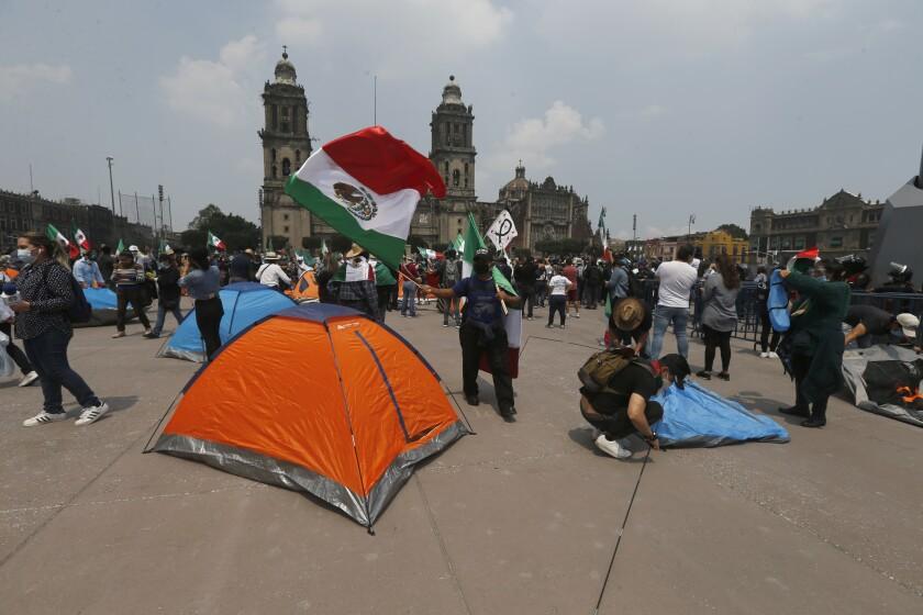 Un manifestante está sentado entre tiendas de campaña instaladas en una protesta