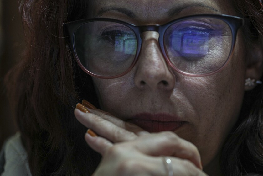 The computer screen is reflected in the glasses of science teacher Marcela Garcia, as she teaches remotely from home while in person classes are cancelled due to the COVID-19 pandemic in Santiago, Chile, Wednesday, June 30, 2021. Garcia teaches sitting on three cushions placed on a chair in her dining room, while many of her students listen to her from their beds because they lack sufficient space. (AP Photo/Esteban Felix)