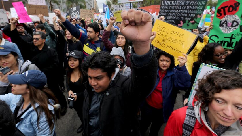 LOS ANGELES, CALIF. - FEB. 18, 2017. Brandon Molina, 18, raises a clenched fist and joins hundreds