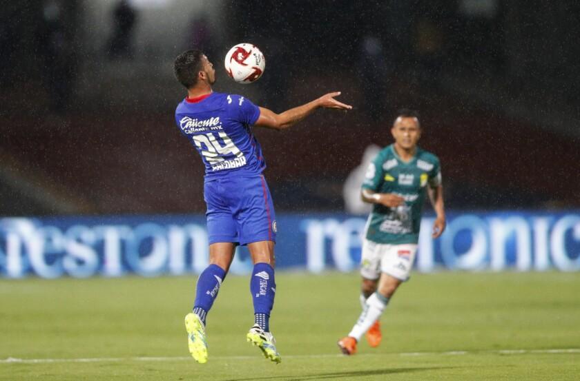 Juan Escobar, izquierda, del Cruz Azul, controla el balón ante Luis Montes, del León