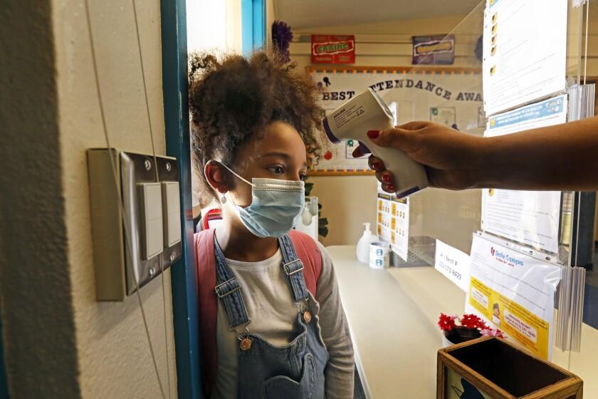 Zadie Williams gets her temperature checked before entering summer school at Hooper Avenue School in  Los Angeles.