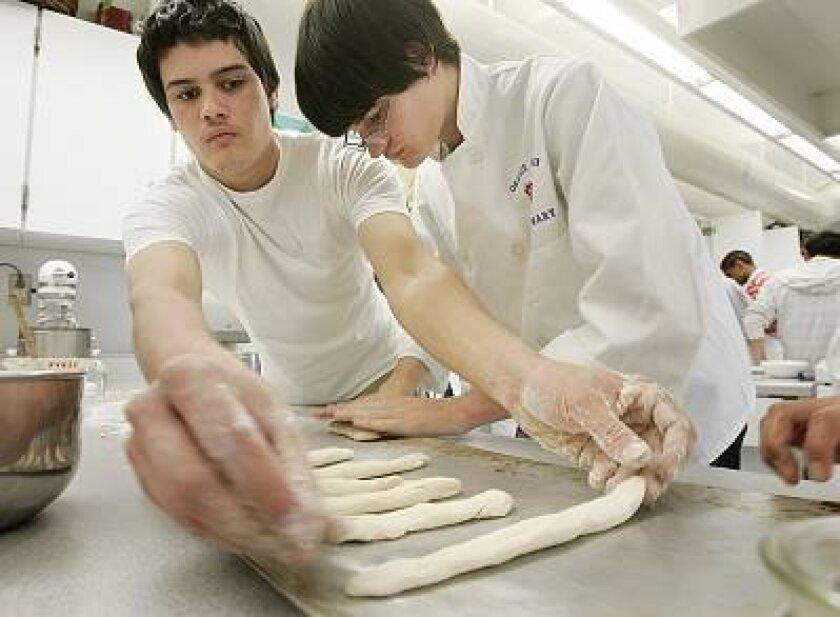 Students Matt Coffman (left) and Ryan Proffitt made breadsticks last month during their culinary arts class at Orange Glen High School.