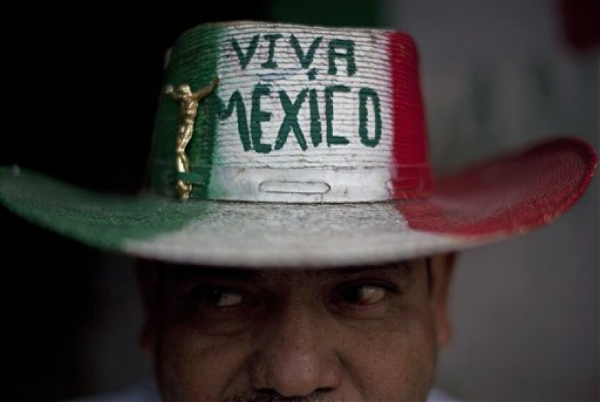 "Street vendor Victor Manuel Jimenez, 44, poses for a portrait outside his home as he wears a hat that reads in Spanish ""Long live Mexico"" in Tijuana, Mexico, Wednesday Oct. 6, 2010. A two-week $5 million festival called Innovative Tijuana starts Thursday Oct. 7, 2010 in the border city across from San Diego and aims to showcase the city's economic prowess and cultural riches in an effort to demonstrate the city is no longer in the grip of warring drug traffickers. (AP Photo/Guillermo Arias)"