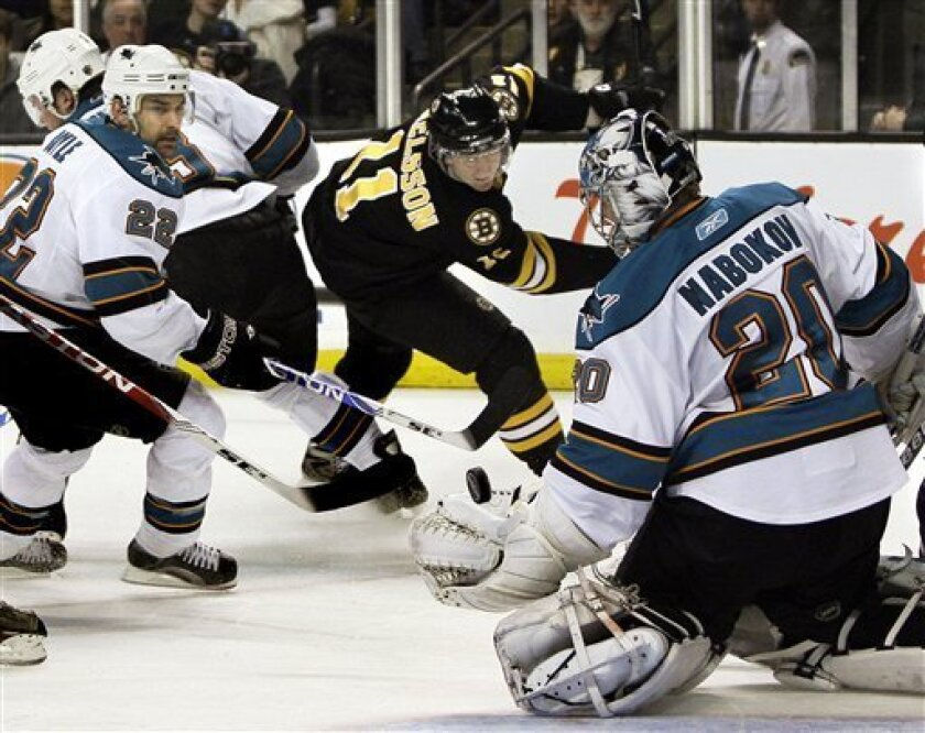 The puck is headed over the glove of San Jose Sharks goalie Evgeni Nabokov (20), of Kazakhstan, but wide of the goal, after Boston Bruins left wing P.J. Axelsson (11) took a shot, while Sharks defenseman Dan Boyle (22) looks on during the second period of an NHL hockey game in Boston on Tuesday, Feb. 10, 2009. (AP Photo/Elise Amendola)