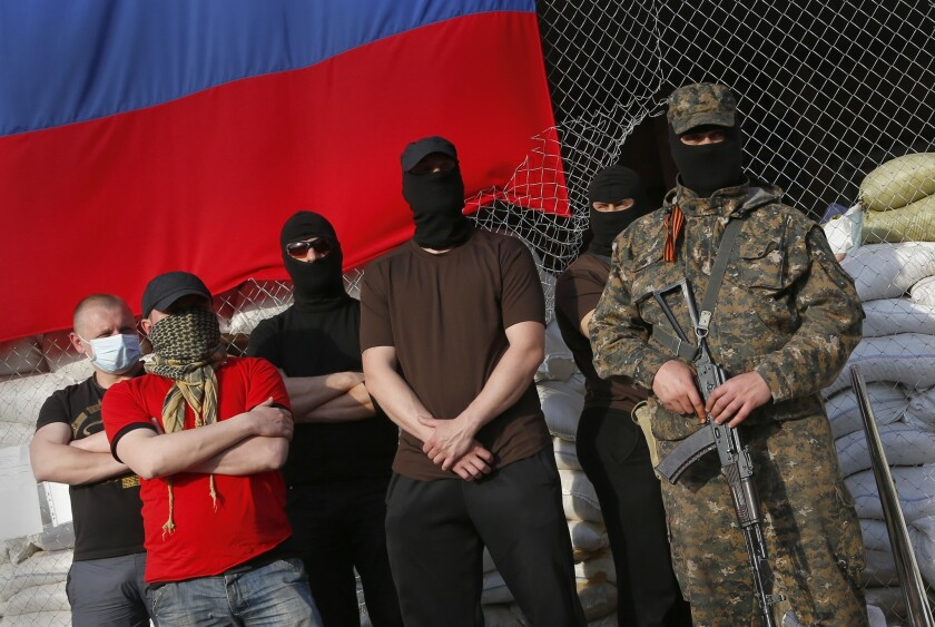 Masked and armed pro-Russia activists stand at the city hall in the Ukrainian city of Slovyansk during negotiations for the release of European military observers being held in eastern Ukraine. The European Union has imposed sanctions on Russia for its role in the rebellion in neighboring Ukraine.
