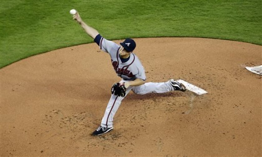 Atlanta Braves' Kris Medlen pitches during the first inning of a baseball game against the Miami Marlins in Miami, Tuesday, April 9, 2013. (AP Photo/J Pat Carter)