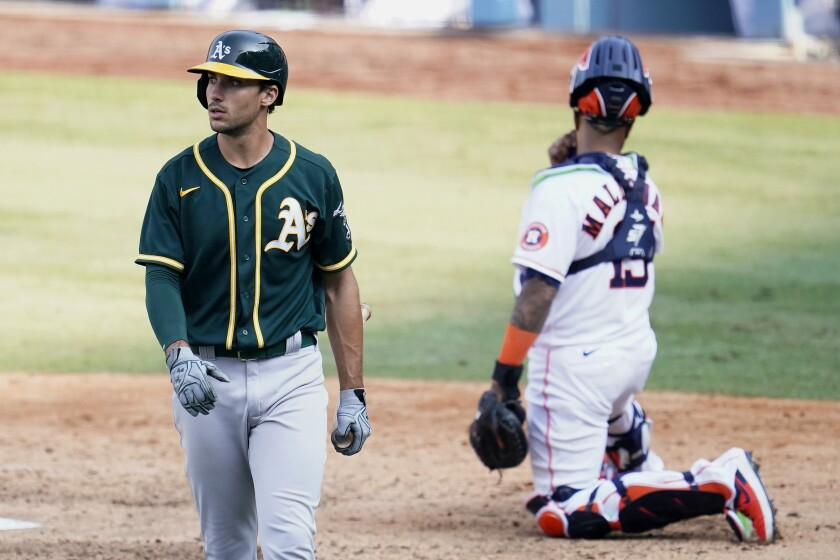 Oakland Athletics' Matt Olson, left, walks to the dugout after striking out against the Houston Astros during the eighth inning of Game 4 of a baseball American League Division Series in Los Angeles, Thursday, Oct. 8, 2020. At right is Astros catcher Martin Maldonado. (AP Photo/Marcio Jose Sanchez)