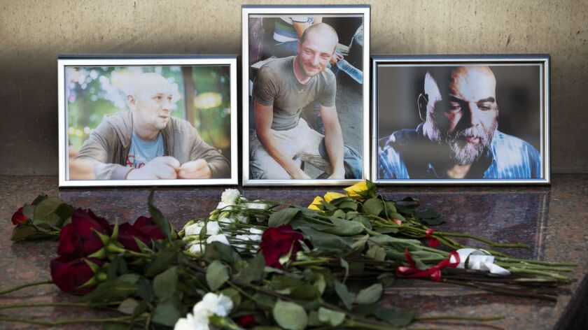 Flowers are placed by portraits of slain journalists Alexander Rastorguyev, Kirill Radchenko and Ork