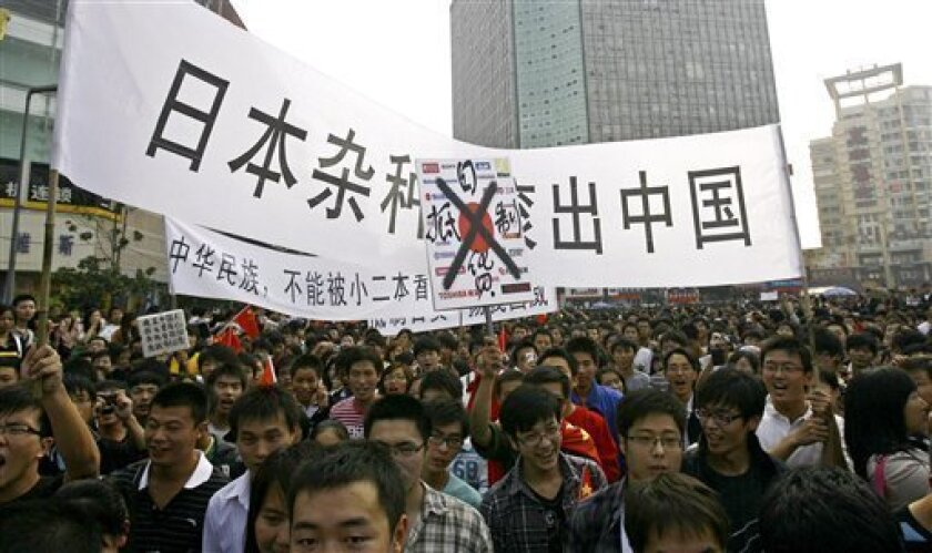 "People hold banners during an anti-Japan protest in downtown Zhengzhou, in central China's Henan province, Saturday, Oct. 16, 2010. Chinese characters on the banners reads, ""Boycott Japanese Products,"" and ""Japanese, Get Out Of China.""(AP Photo)"