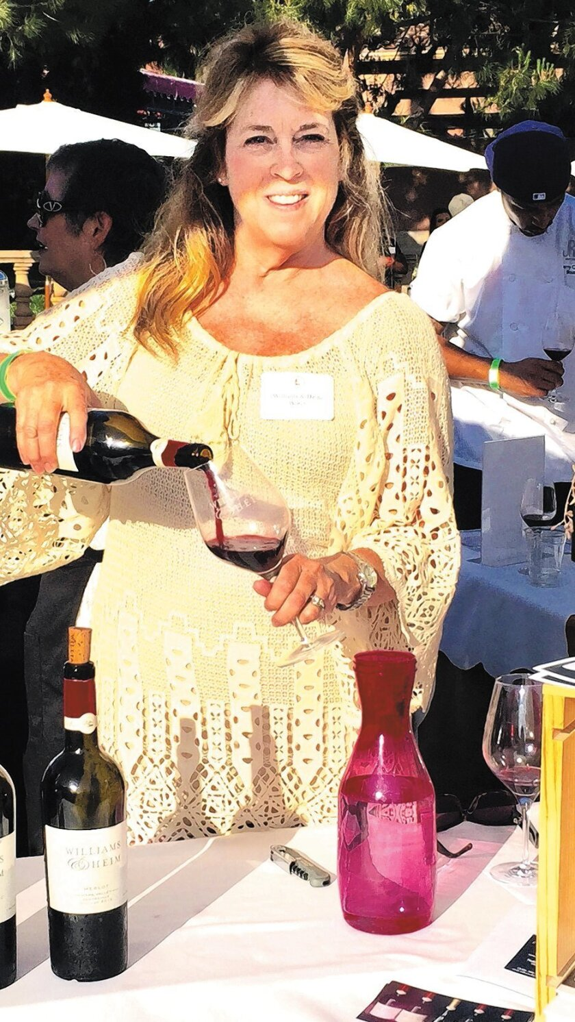 Mare Williams pours 2012 Williams & Heim Triple Entendre, a Bordeaux style blend, at the Wine & Roses event.