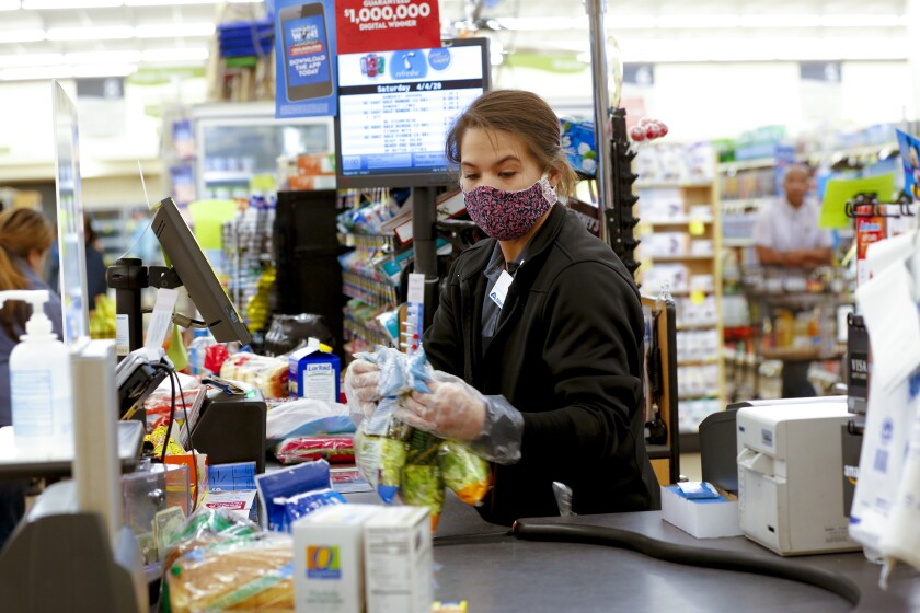 In this file photo, a cashier at the Albertsons in San Carlos wore a required cloth mask. Below, the president of the United Food and Commercial Workers Union, Local 135, asks patrons to follow a few guidelines while shopping.
