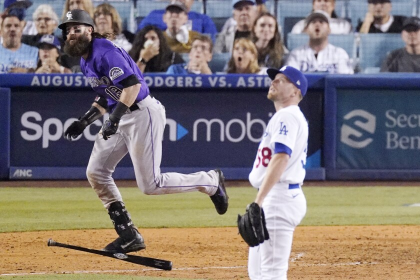 The Rockies' Charlie Blackmon runs after hitting a two-run homer off Dodgers reliever Jimmie Sherfy in the 10th inning.
