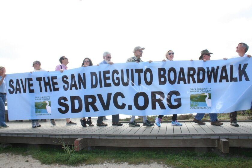 "Holding a 20-foot-long ""Save the Boardwalk"" banner, several elected officials joined the effort to keep the San Dieguito boardwalk intact."
