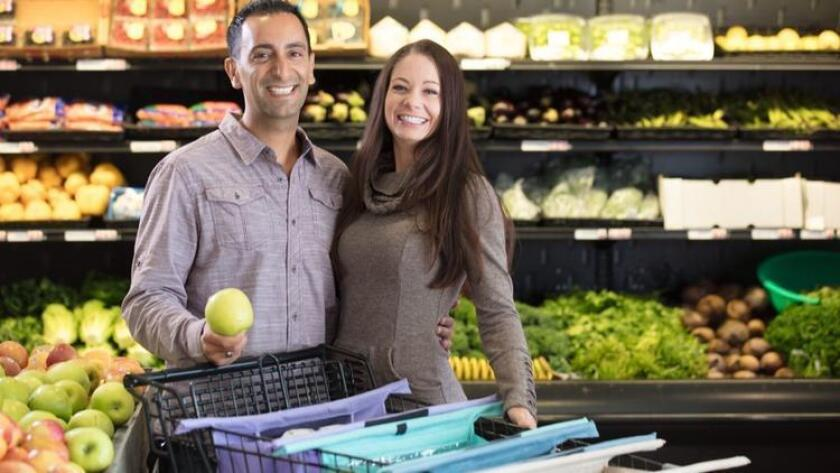Carlsbad residents Farzan and Jen Dehmoubed with their Lotus Trolley Bag, a new reusable shopping bag system that folds up into an over-the-shoulder bag. (Lotus Trolley Bag)