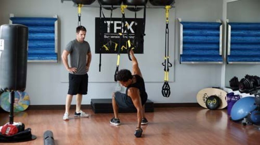 A Bird Rock Fit trainer works with a client using a TRX and free weights. Photo: Courtesy