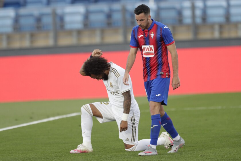 Real Madrid's Marcelo takes a knee as he celebrates his goal during the Spanish La Liga soccer match between Real Madrid and Eibar at Alfredo di Stefano stadium in Madrid, Spain, Sunday, June 14, 2020. (AP Photo/Bernat Armangue)