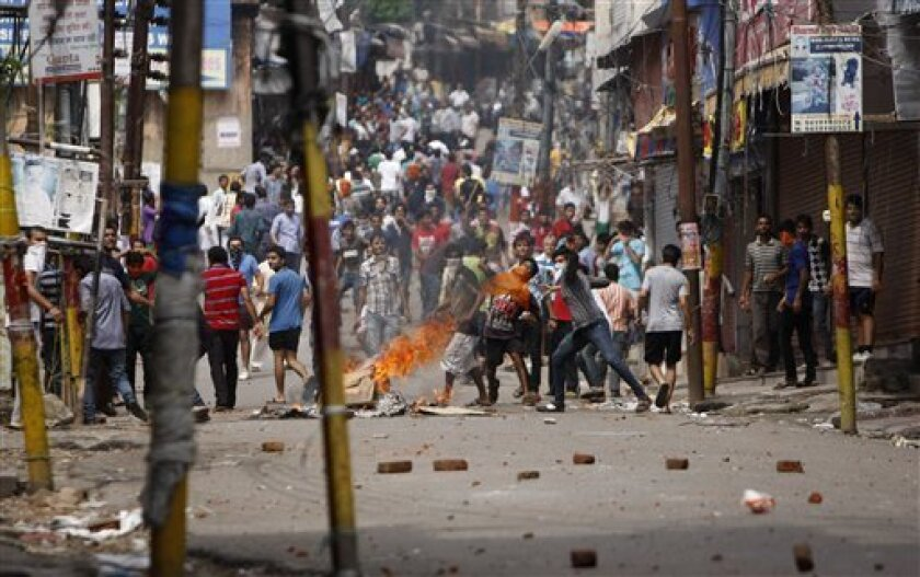 Indian Hindu protesters throw stones at policemen during a protest after rival communities clashed in Kishtwar, in Jammu, India, Saturday, Aug. 10,2013. Indian forces fired warning shots Saturday to enforce a curfew and to push angry people back into their homes in Kishtwar, in the Indian portion of Kashmir where clashes between Muslims and Hindus during Eid celebrations killed at least two people and injured another 24.(AP Photo/Channi Anand)