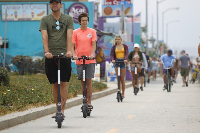 People on scooters in Pacific Beach before they were banned from city boardwalks in February 2020.