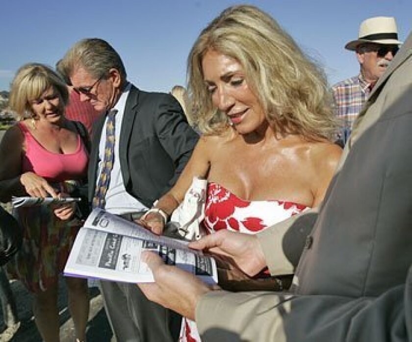 Rosie Goldstein (center), at the races yesterday with friend Maggie Bacon (left) and racetrack CEO Joe Harper, was named Del Mar's first Miss Cougar.  (Earnie Grafton / U-T)