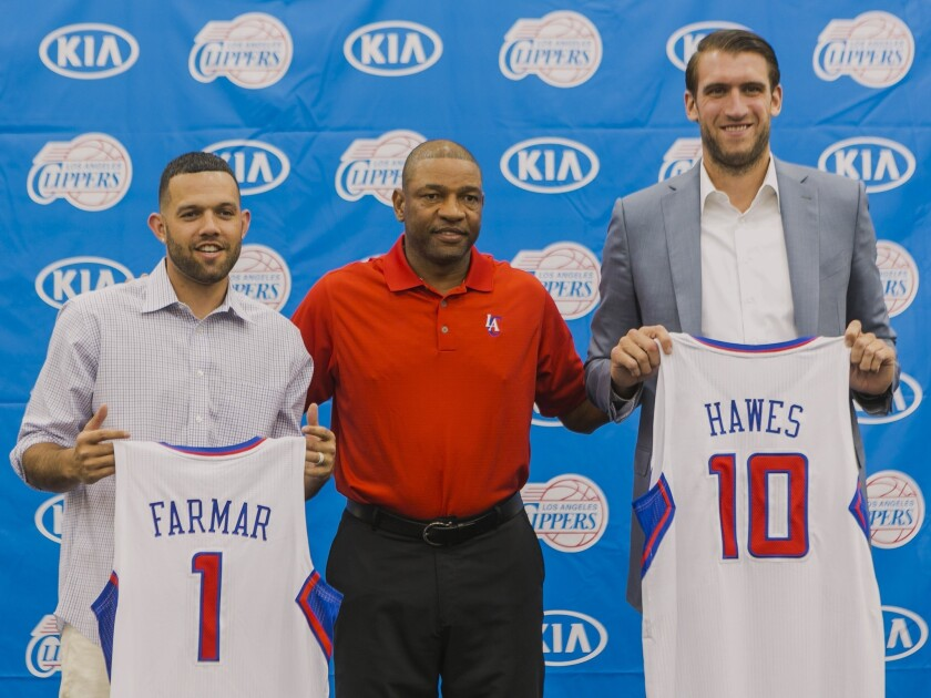 Clippers Coach Doc Rivers, center, stands with his team's two newest members, former Lakers guard Jordan Farmar, left, and big man Spencer Hawes, right, who last played for Cleveland.