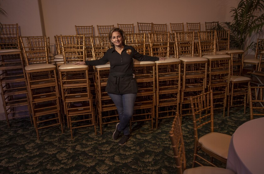 Ann Lancaster leans against rows of stacked chairs in a closed indoor-dining area of her restaurant.