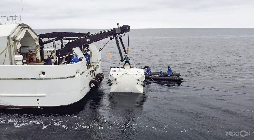 """In this handout photo taken in Jan. 2020 and provided by Nekton, scientists lower the """"Limiting Factor"""" submarine into the Mediterranean Sea, part of sea trials before the next stage of the Nekton Mission begins in mid-March. A team of scientists is preparing to dive deep into the depths of the Indian Ocean - into a """"Midnight Zone"""" where light barely reaches, but life still thrives. Scientists from the British-led Nekton Mission plan to survey wildlife and gauge the effects of climate change in the unexplored area. (Nekton via AP)"""