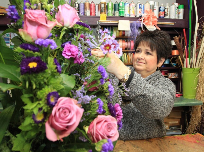 Robin Heller of Flowers by David in Langhorne, Pa., works on a sympathy arrangement.